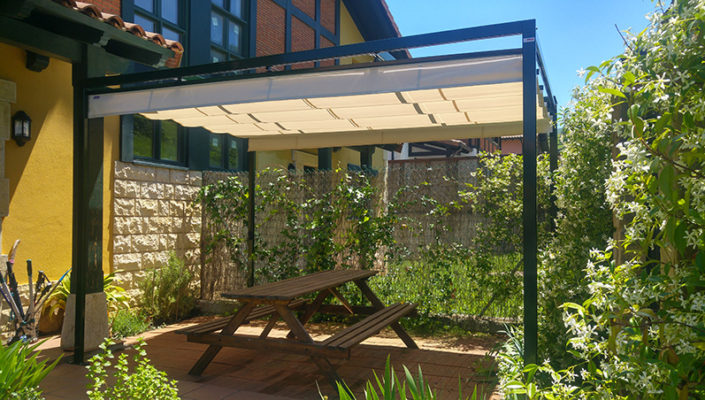 Pérgola de aluminio con lona amarilla en la terraza de una vivienda y con una mesa de picnic