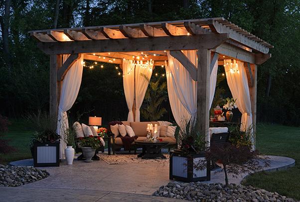 Pérgola de madera con telas y zona chill out con sofás y guirnaldas